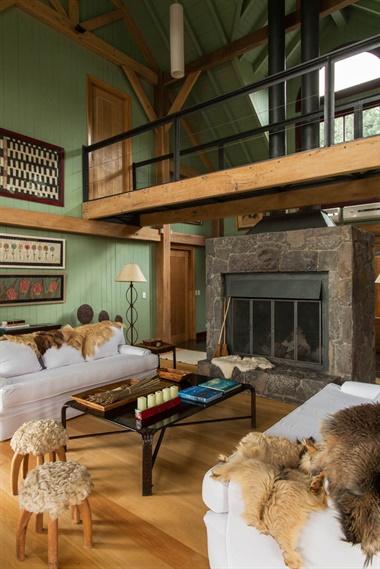 El living tiene el clima perfecto de una típica cabaña de invierno. Además de la chimenea de piedra y hierro, lo que más llama la atención es el puente, con perfiles de hierro, pensado para aprovechar la altura del galpón.