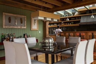 Desde la cocina, se destaca la campana en negro. La barra está hecha con maderas que sobraron de la obra. En las paredes del comedor integrado, se ven cuadros hechos por el dueño de casa