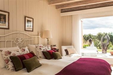 En suite, el cuarto principal tiene un gran ventanal que integra el ambiente con la naturaleza. Las paredes son de madera y las vigas patinadas en tonos neutros. La ropa de cama mantiene los colores de la casa, verde y bordó
