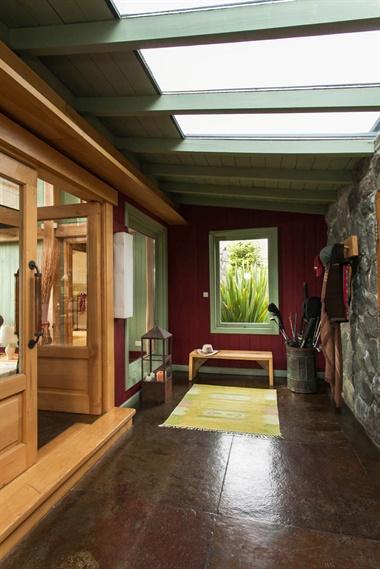 Con una pared de piedra, el hall frío da la bienvenida. En los días fríos es el lugar para despojarse de toda la ropa de abrigo. Aquí, los colores están invertidos con respecto al resto de la casa: el bordó está en el fondo y el verde en las carpinterías