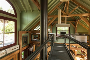 Desde el puente de planta alta se puede ver el escritorio, que también funciona como cuarto de huéspedes. También, la combinación entre el verde de las paredes y el bordó de las carpinterías que se repite en el resto del loft
